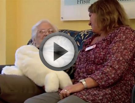 Eine demenzkranke Seniorin kuschelt mit der computergesteuerten Kuschelrobbe Paro.