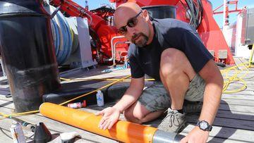 Foto, das einen Forscher mit einem Haizahn und Magnetometer zeigt