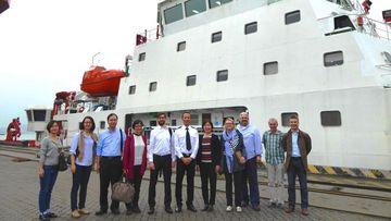 Foto, dass Menschen vor einem Schiff zeigt