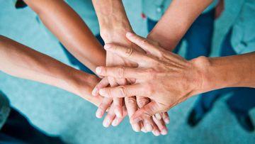 Foto, das mehrere Hände übereinander gelegt zeigt
