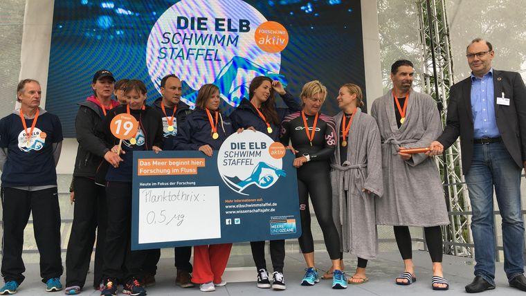 Die Teilnehmenden der 19. Etappe der Elbschwimmstaffel auf der Bühne der Abschlussveranstaltung