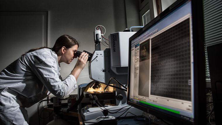 Eine Forscherin arbeitet am Mikroskop.