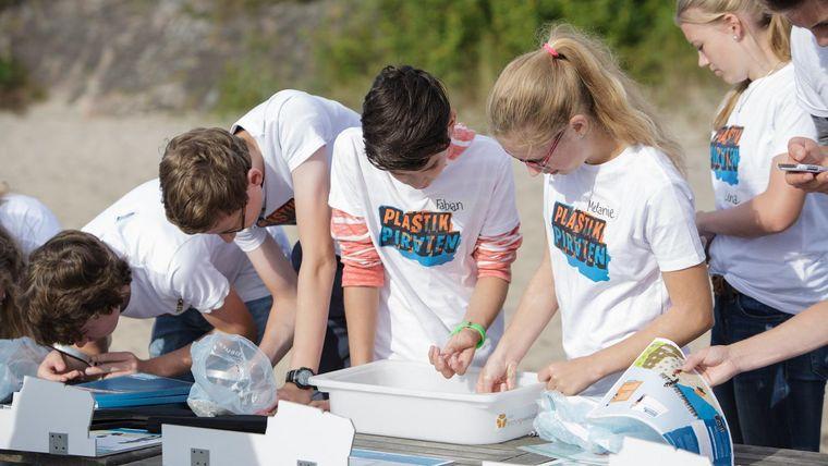 Eine gruppe Jugendliche untersucht ihre Funde