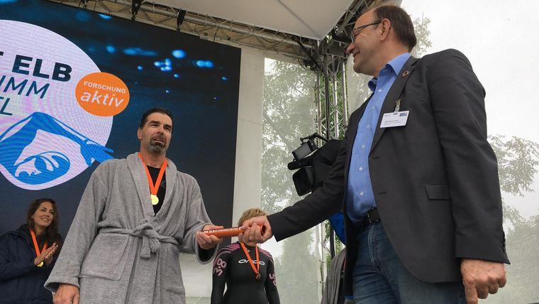 Jens, der letzte Schwimmer der Elbschwimmstaffel, übergibt den Staffelstab zurück an Rudolf Leisen, Projektgruppe Wissenschaftsjahr Meere und Ozeane im Bundesministerium für Bildung und Forschung