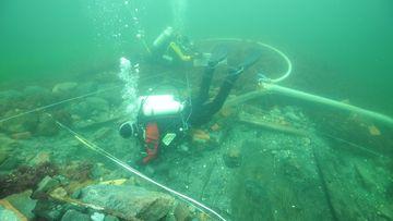 Foto von Tauchern, die ein gesunkenes Schiff untersuchen