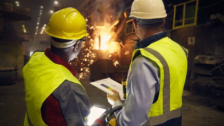 Steelworkers with digital tablet and clipboard talking in steel mill