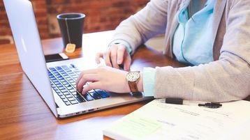 Symbolbild: Ein Laptop steht auf einem Tisch. Eine Person sitzt davor mit Ihren Händen auf der Tastatur. Auf dem Tisch befinden sich ebenfalls Unterlagen und eine Tasse Tee, sowie ein Smartphone. Veränderungen auf dem Ausbildungsmarkt wirken sich auch auf die Arbeitswelten der Zukunft aus.